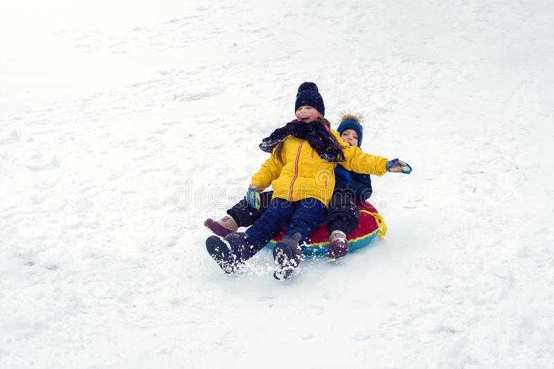 Happy children sledding tubing. brother and sister play together in winter. children slide down the hill. kids laugh and scream royalty free stock photography