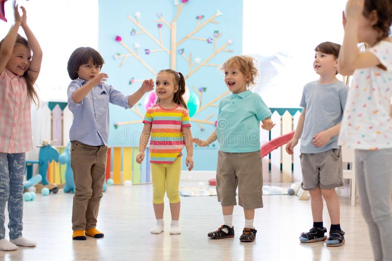 Happy children stand semicircle on floor in kindergarten or day care centre. Preschool kids having fun indoors, playing stock images