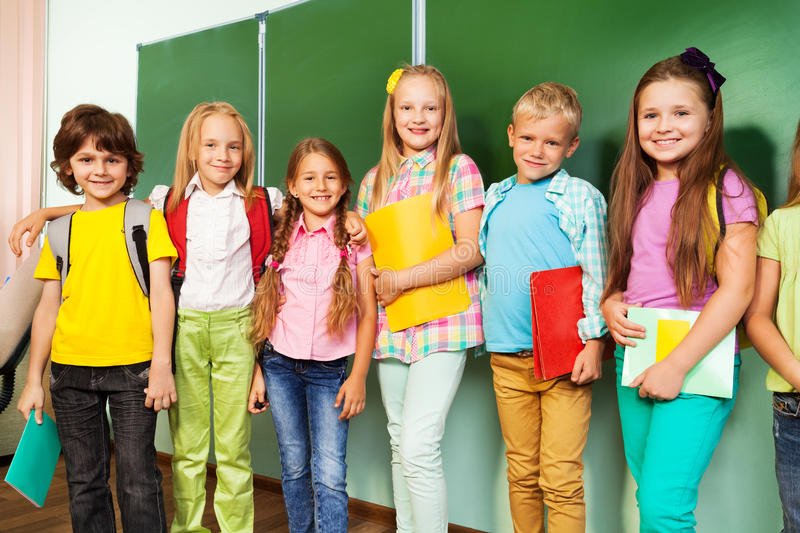 Happy children stand with text books in row stock photography