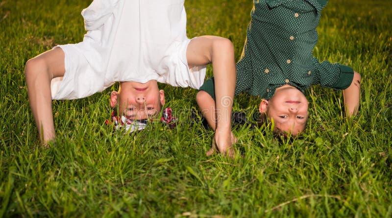 Happy children standing upside down on green grass stock photos
