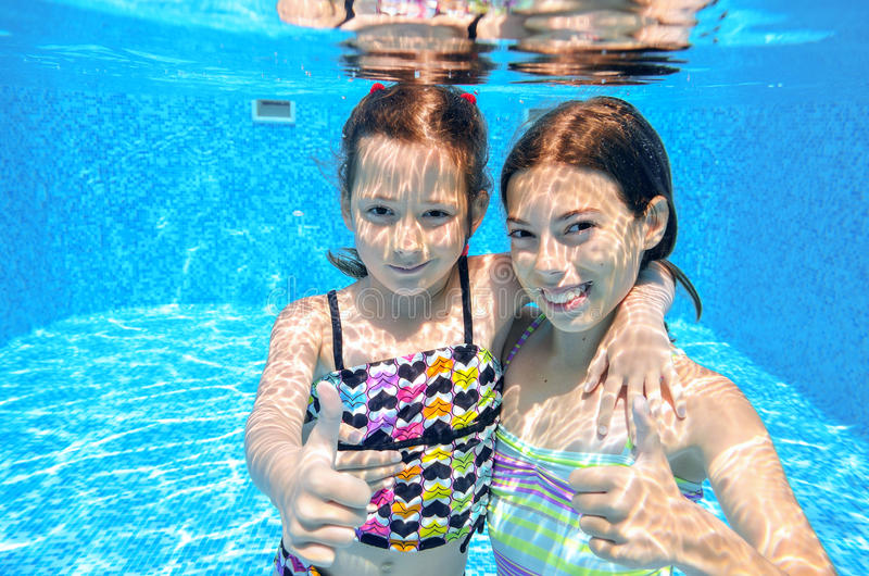 Happy children swim in pool underwater, girls swimming. Playing and having fun, kids water sport royalty free stock photo