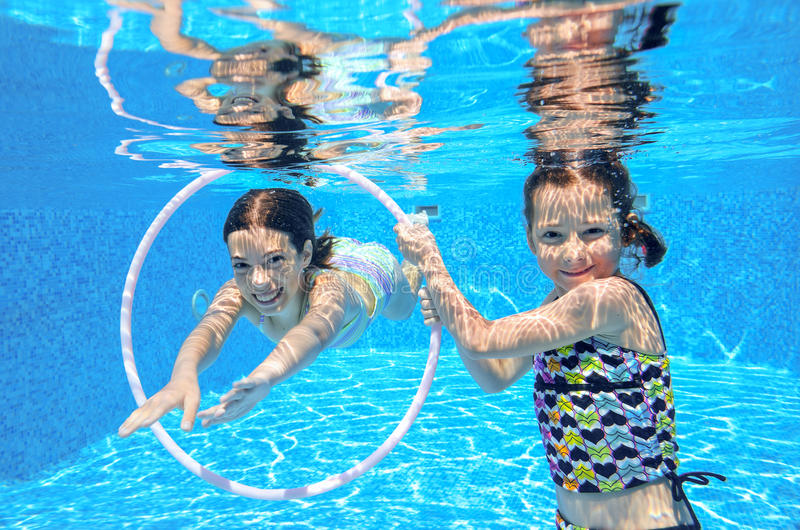 Happy children swim in pool underwater, girls swimming. Playing and having fun, kids water sport royalty free stock images