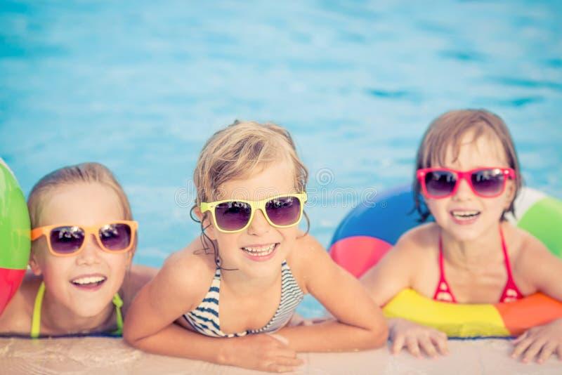 Happy children in the swimming pool stock photos
