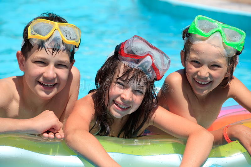 Happy children in swimming pool. Three happy, smiling children on an inflatable mattress in a swimming pool stock photos