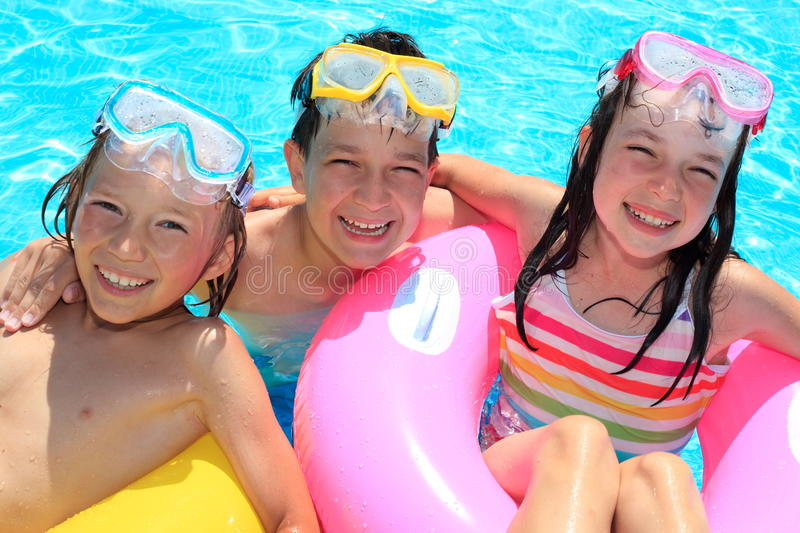 Happy children in swimming pool. Three happy, smiling children playing in swimming pool royalty free stock image