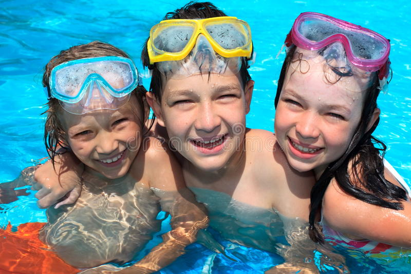 Happy Children in Swimming Pool. Three children with swim goggles smiling in swimming pool royalty free stock photos