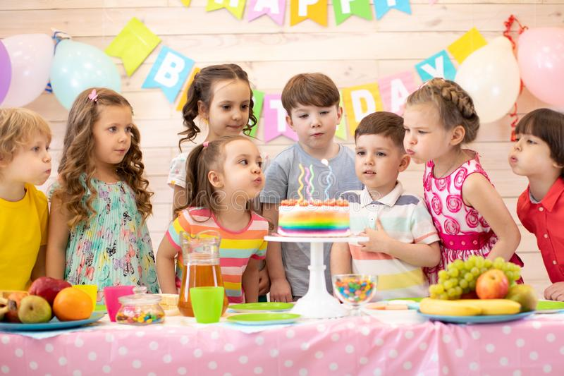 Children at table celebrating birthday holiday. Kids blows together candles on festive cake stock images
