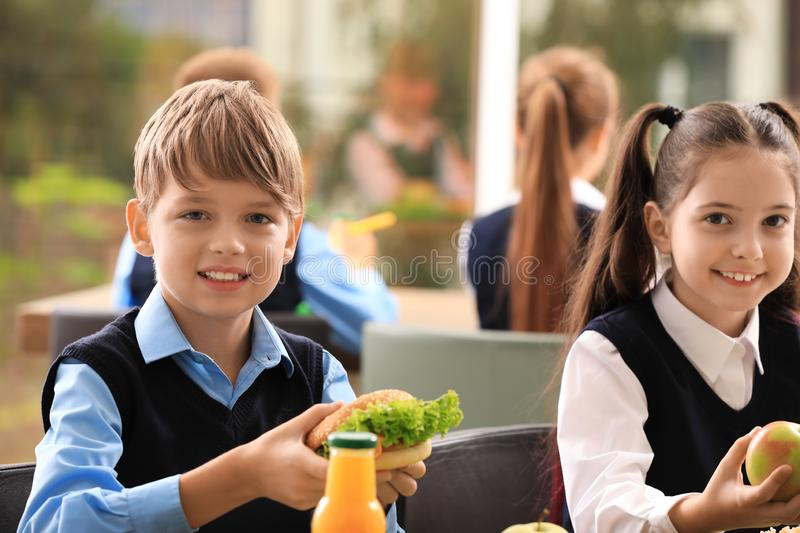 Happy children at table with  food in school canteen stock image