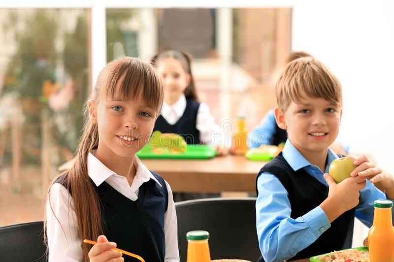 Happy children at table with healthy food royalty free stock photography