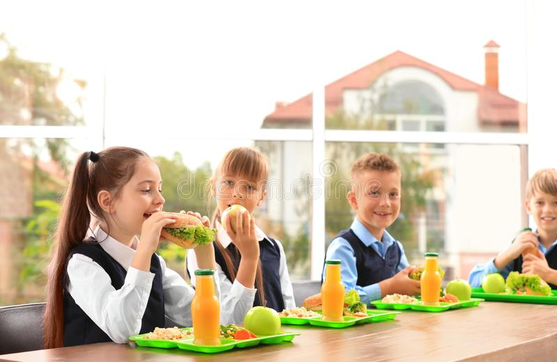 Happy children at table with healthy food stock photo