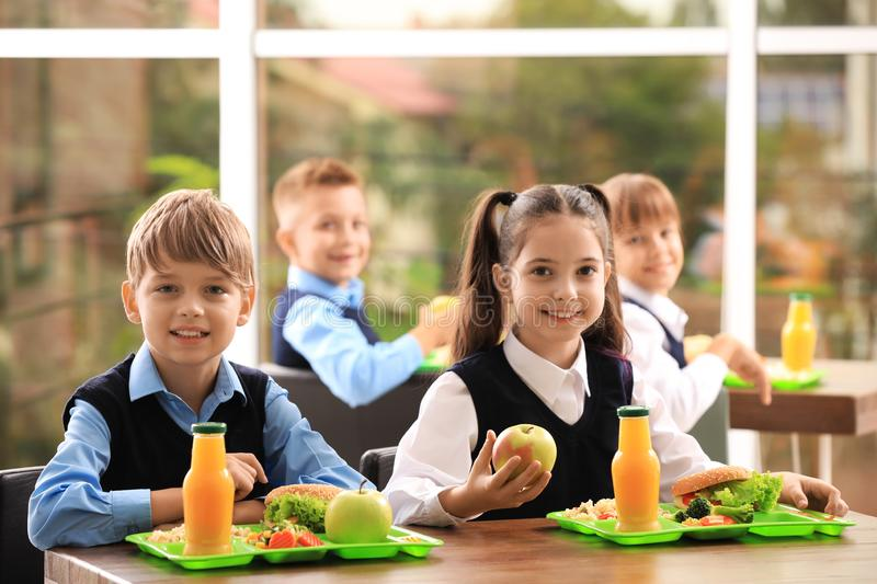 Happy children at table  healthy food in school canteen stock photography