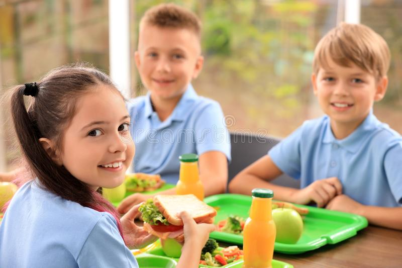 Happy children at table with healthy food in canteen stock photography