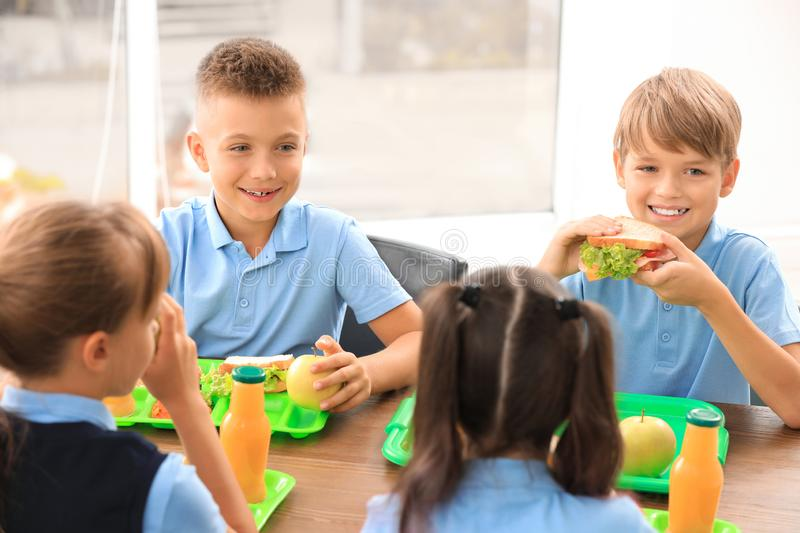 Happy children at table with healthy food stock image