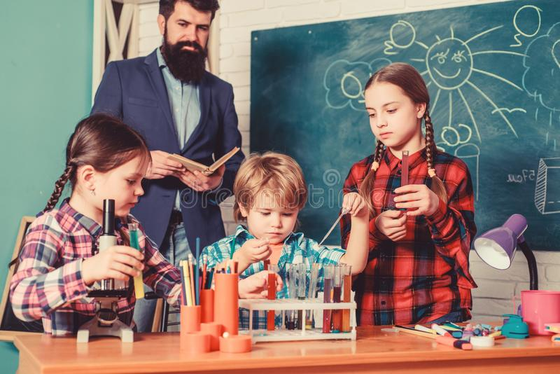 Happy children teacher. doing experiments with liquids in chemistry lab. chemistry lab. back to school. kids in lab stock photography