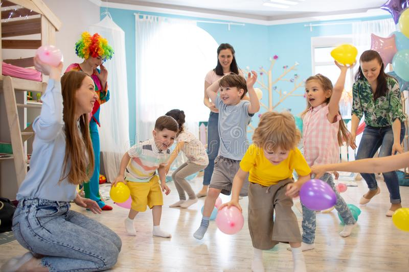 Happy children and their parents entertain and have fun with color balloon on birthday party stock photos
