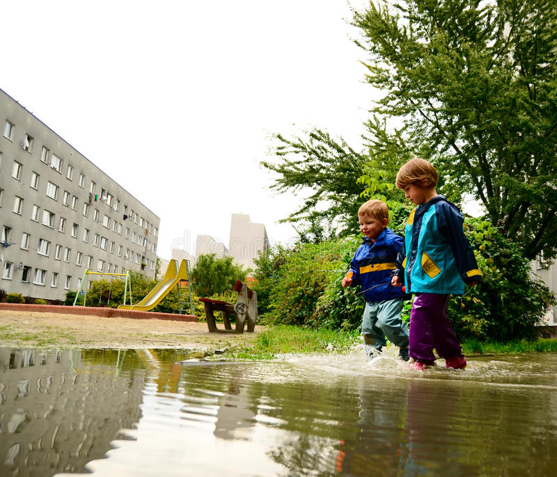 Happy children in water-proof clothes running through the puddle after the rain. Children in special clothes running through puddle after the rain stock photography