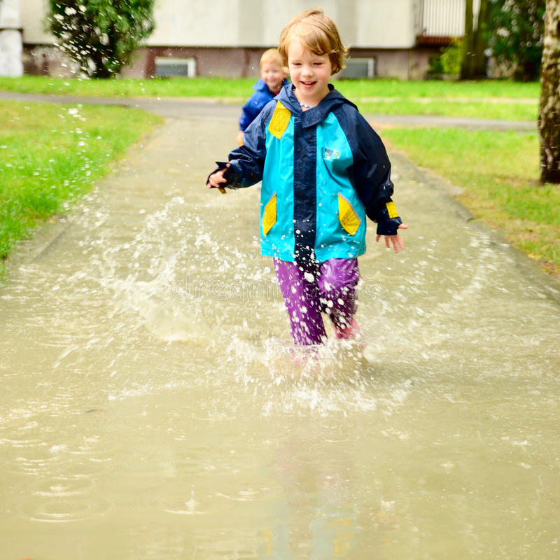 Happy children in water-proof clothes running through the puddle after the rain. Two children running through the water after the rain royalty free stock images