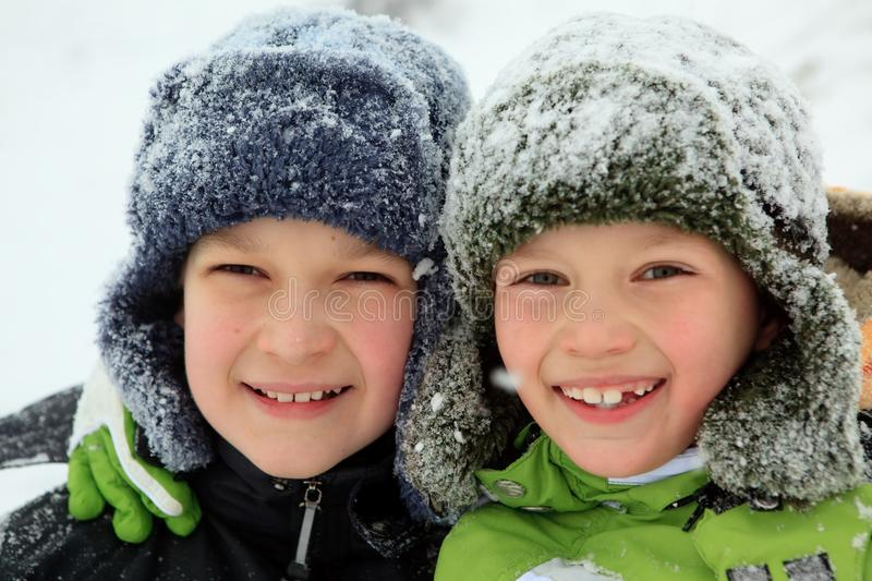 Happy children in winter hats. Closeup of smiling young brothers in snow covered wintry hats royalty free stock photo