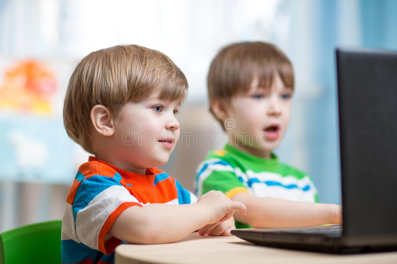 Happy children working at laptop. Happy children boys working at laptop indoors royalty free stock image