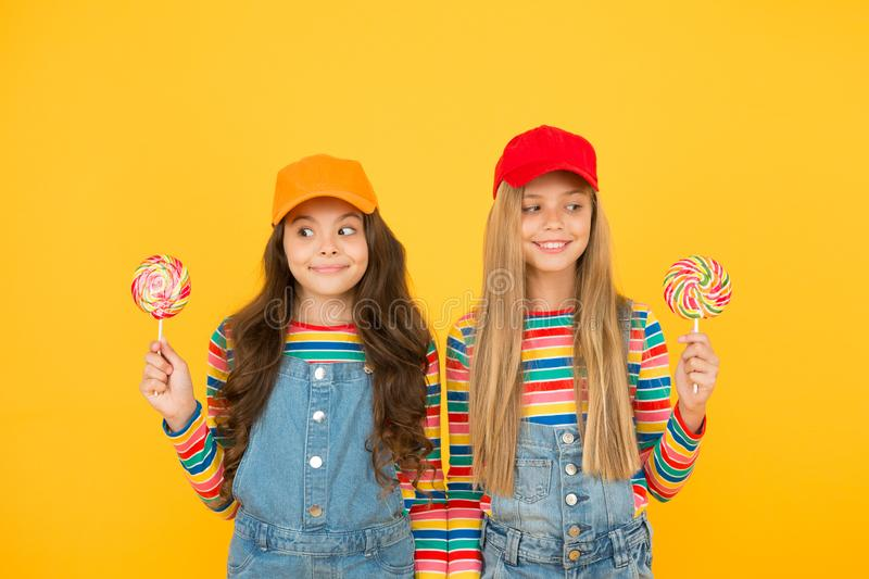 Happy childrens day. cute sisters lollipop candy. cheerful kids have party fun. school friends enjoy holiday celebration royalty free stock photo