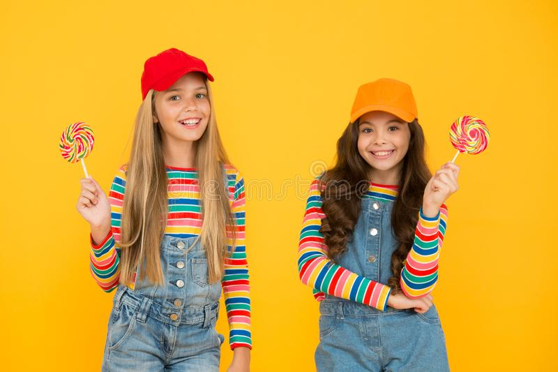 Happy childrens day. Holiday celebration. Happy girls eating lollipop candy. Fun and entertainment. Join celebration. Universal childrens day. Child care stock photos