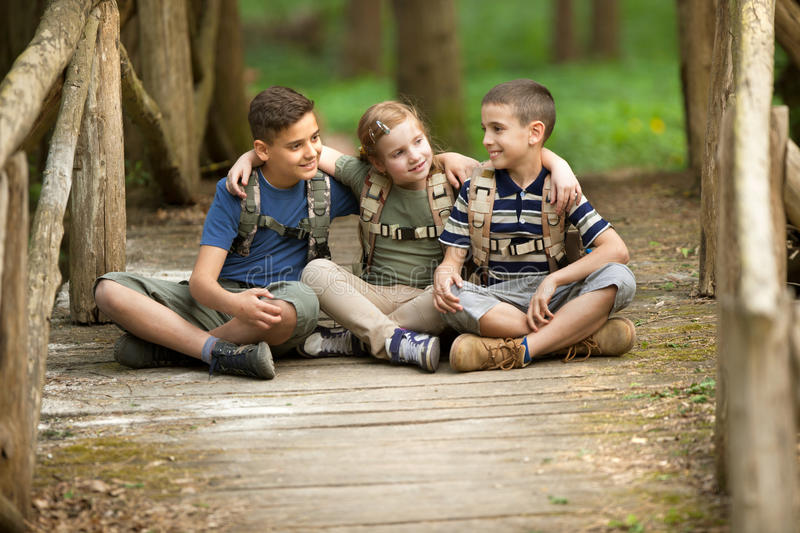 Happy childs in green forest playing,concept of kids vacations a. Young scouts sitting on old wooden bridge in the woods stock images
