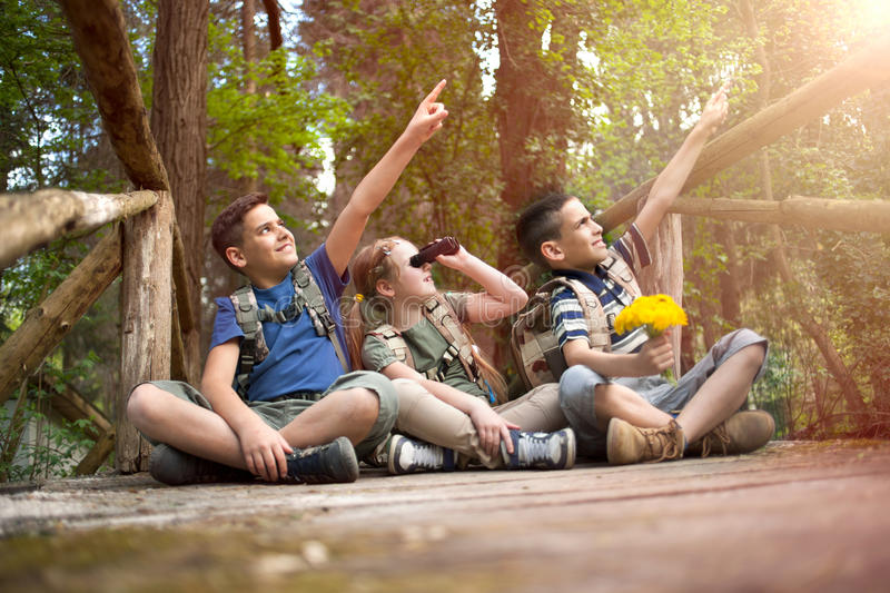 Happy childs in green forest playing,concept of kids vacations a. Young scouts sitting on old wooden bridge in the woods royalty free stock photos