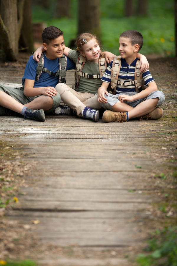 Happy childs in green forest playing,concept of kids vacations a. Young scouts sitting on old wooden road in forest stock photography