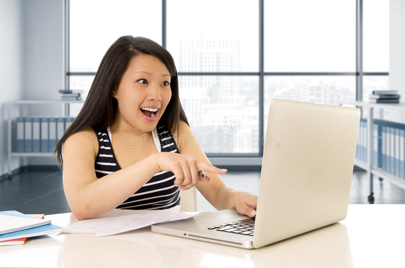 Happy chinese asian woman working and studying on her computer sitting at modern office desk smiling cheerful stock photography