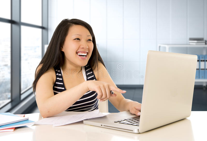 Happy chinese asian woman working and studying on her computer sitting at modern office desk smiling cheerful royalty free stock photo
