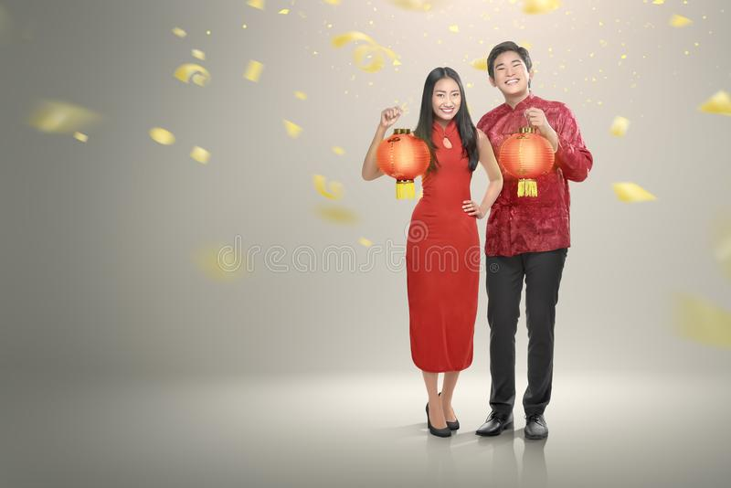 Happy chinese couple in cheongsam clothes holding red lanterns royalty free stock photos