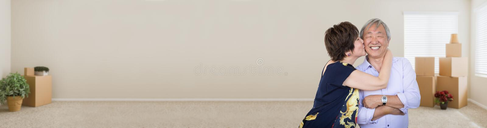 Happy Chinese Couple Kissing in Empty Room with Moving Boxes. Banner stock image