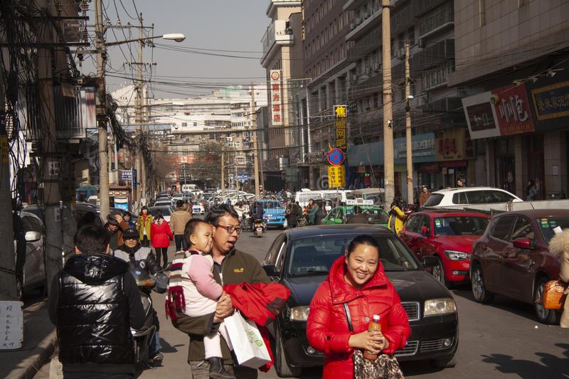 A happy Chinese family walking in a busy street in Beiling, China together with other people, cars and mopeds royalty free stock image