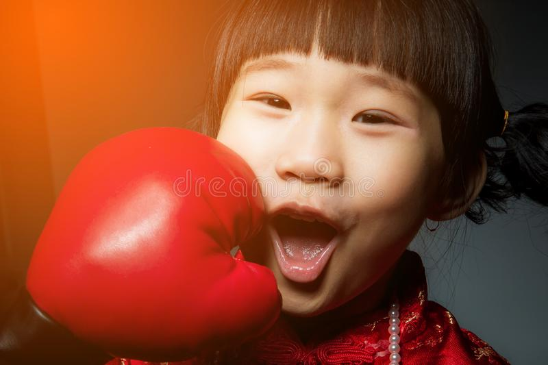 Happy chinese girl getting a hard punch from boxing glove fist. stock image