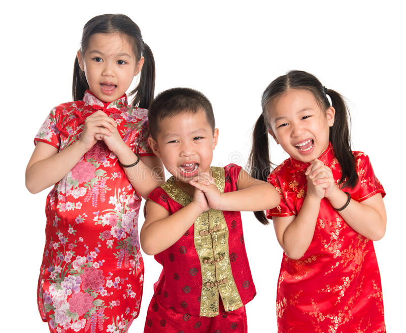 Happy Chinese New Year. Little oriental children wishing you a happy Chinese New Year, with traditional Cheongsam standing isolated on white background royalty free stock photos