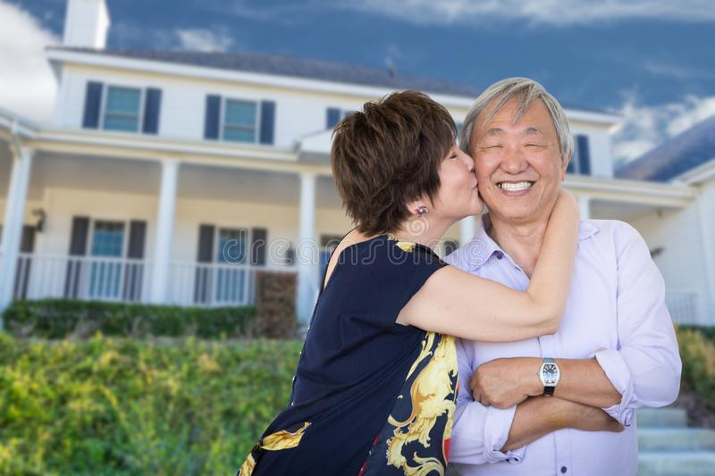 Happy Chinese Senior Adult Couple Kiss In Front Of Custom Home. Happy Chinese Senior Adult Couple Kissing In Front Of Custom House stock image