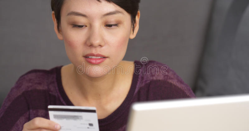 Happy Chinese woman buying things online stock photography