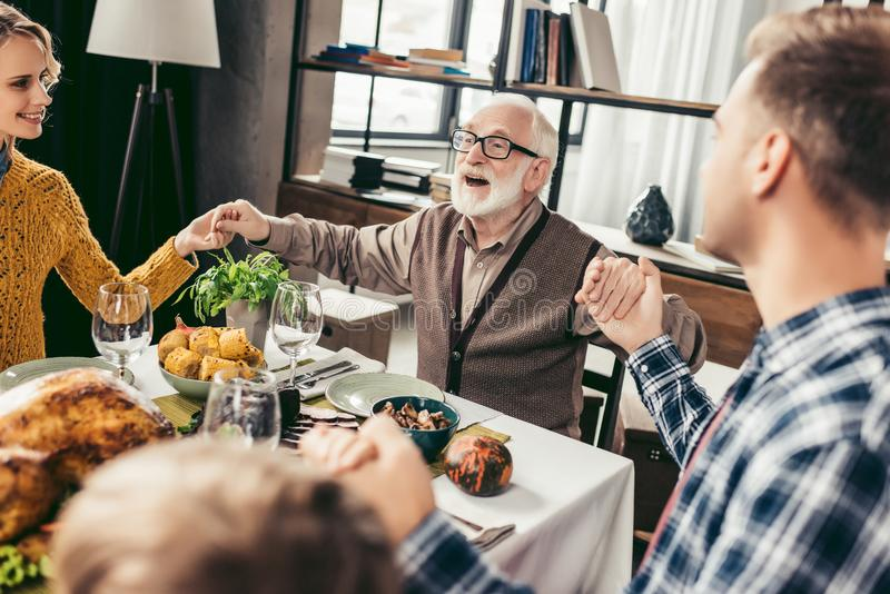 Happy christian family praying before holiday dinner. And holding hands stock photography