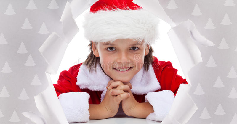 Happy christmas boy smiling through hole in wrapping paper royalty free stock photography