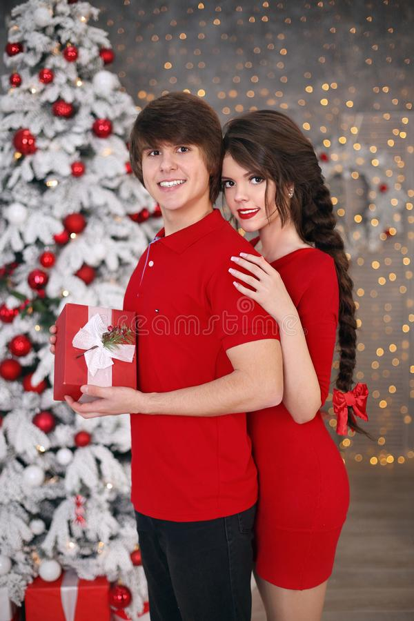 Happy Christmas couple embrace in red clothes. Young brunette gi royalty free stock photos