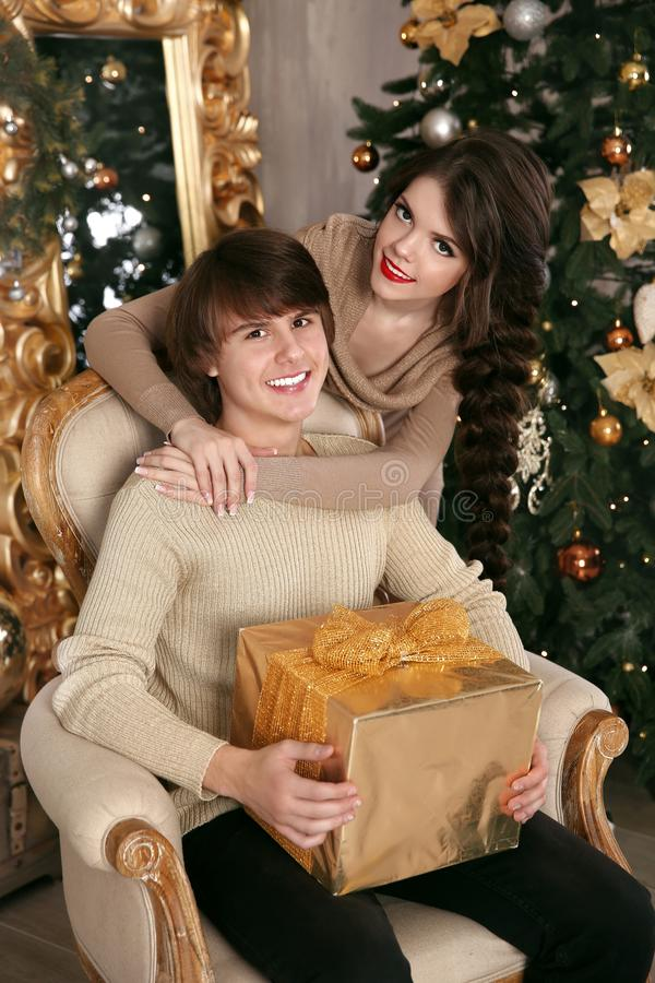 Happy Christmas couple in love. Young brunette girl hugging hand royalty free stock image
