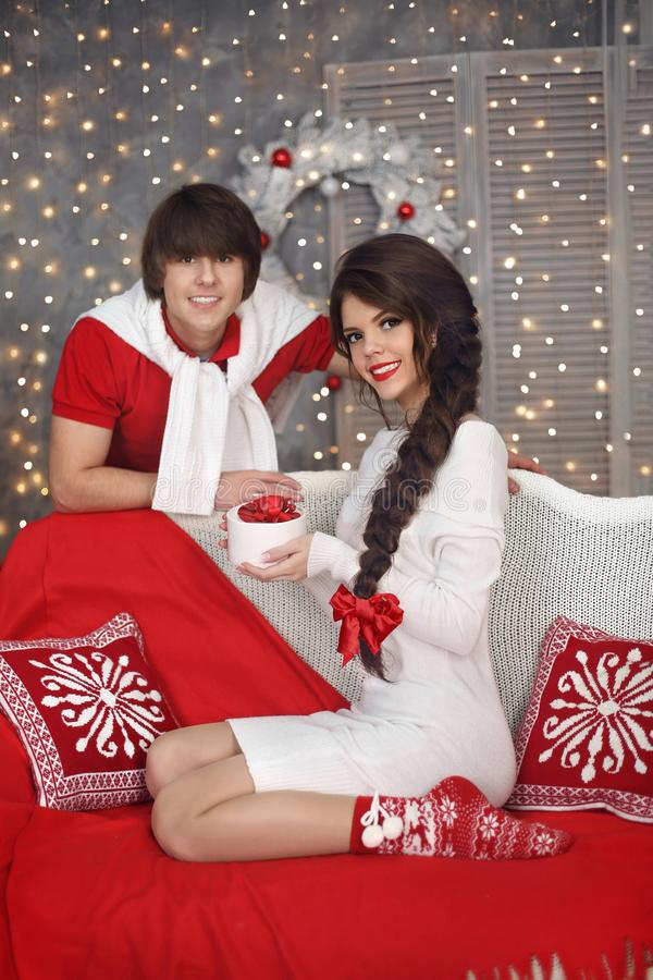 Happy Christmas couple in love. Young handsome man present gift stock images
