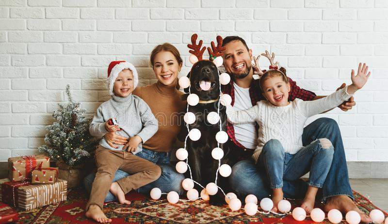 Happy Christmas! family mother father and kids with dog before Christmas with garland   and tree stock photo