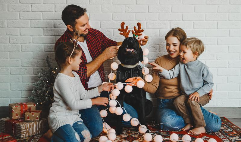 Happy Christmas! family mother father and kids with dog before Christmas with garland   and tree stock photography