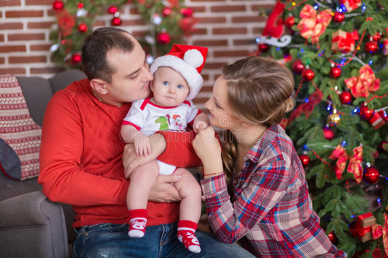 Happy Christmas Family portrait. Smiling Parents with baby daughter at Home Celebrating New Year. Christmas Tree. Happy Christmas Family portrait. Smiling royalty free stock photography