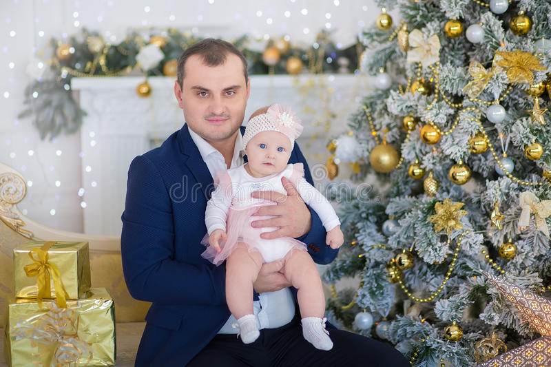 Happy Christmas Family portrait. Smiling Parents with baby daughter at Home Celebrating New Year. Christmas Tree stock photos