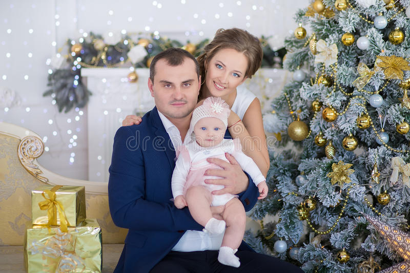 Happy Christmas Family portrait. Smiling Parents with baby daughter at Home Celebrating New Year. Christmas Tree royalty free stock photo