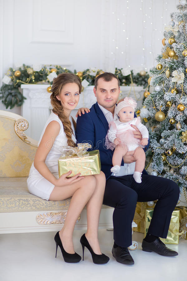 Happy Christmas Family portrait. Smiling Parents with baby daughter at Home Celebrating New Year. Christmas Tree royalty free stock image