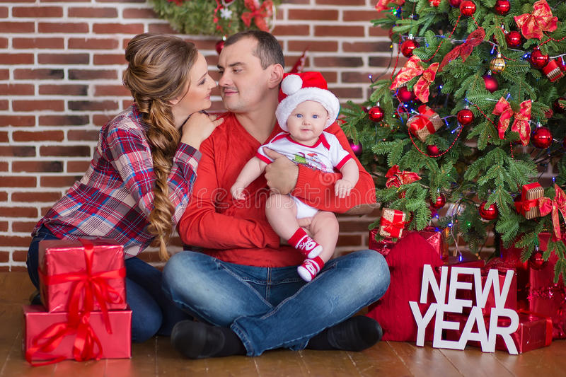 Happy Christmas Family portrait. Smiling Parents with baby daughter at Home Celebrating New Year. Christmas Tree stock images