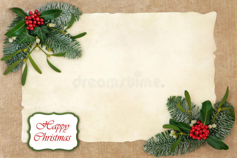 Happy Christmas Floral Border. Abstract background border with happy christmas sign with flora of holly, ivy, mistletoe and snow covered fir on parchment over royalty free stock images